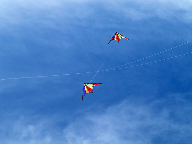 Two kites in the sky with tangled up ropes stock photo