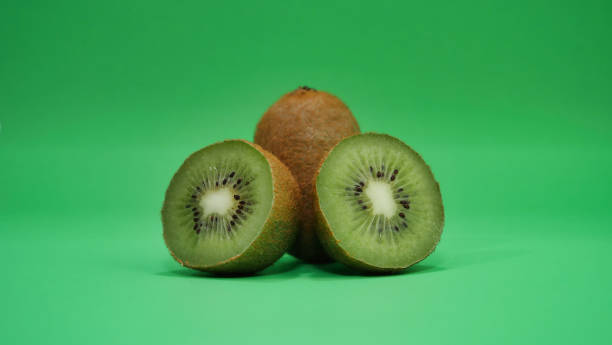 two kiwis one is cut on a green background stock photo