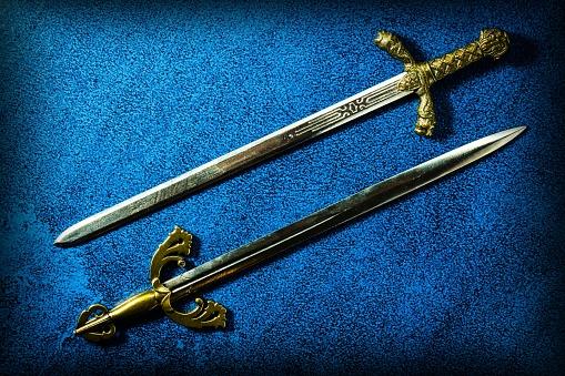 https://media.istockphoto.com/photos/two-knightly-swords-lie-in-parallel-on-a-dark-blue-background-view-picture-id1193919063?k=6&m=1193919063&s=170667a&w=0&h=6bXFvP_Tm0okBTtYrPx06cGy0lzrwxBHGEtKjxQYezU=