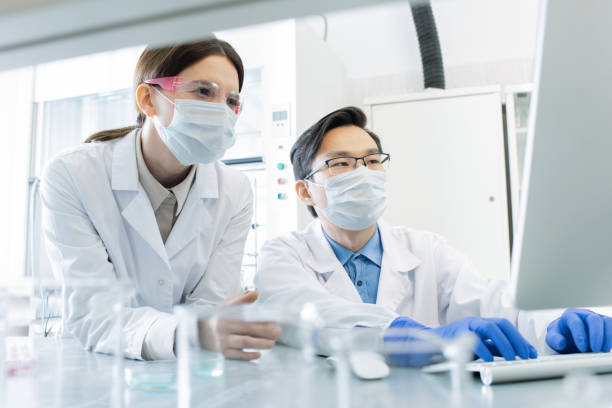 two lab workers in masks, eyeglasses and whitecoats looking at computer screen - ricerca scientifica foto e immagini stock