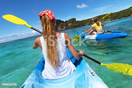 istock Two ladies at sea kayaks walking in blue lagoon 898500306