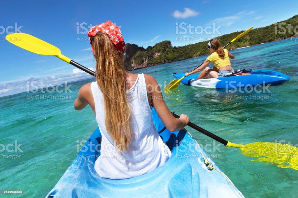 Dos señoras en kayaks de mar en laguna azul - foto de stock