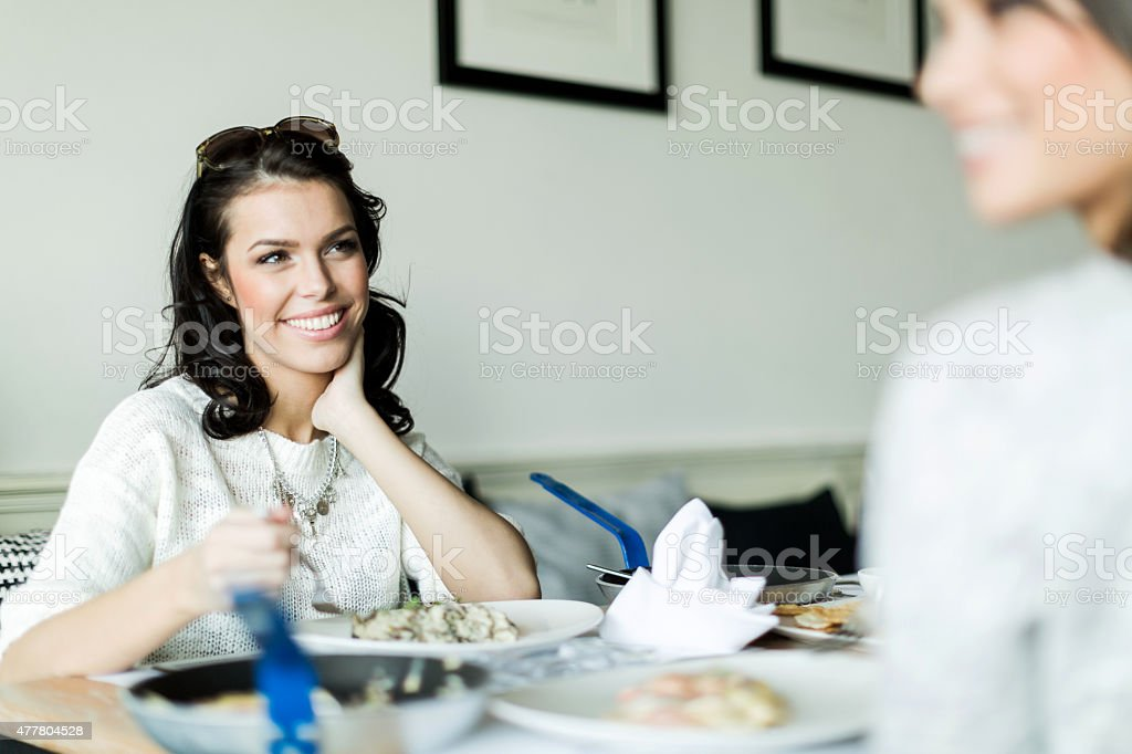 Two ladies eating in a restaurant while having a conve stock photo