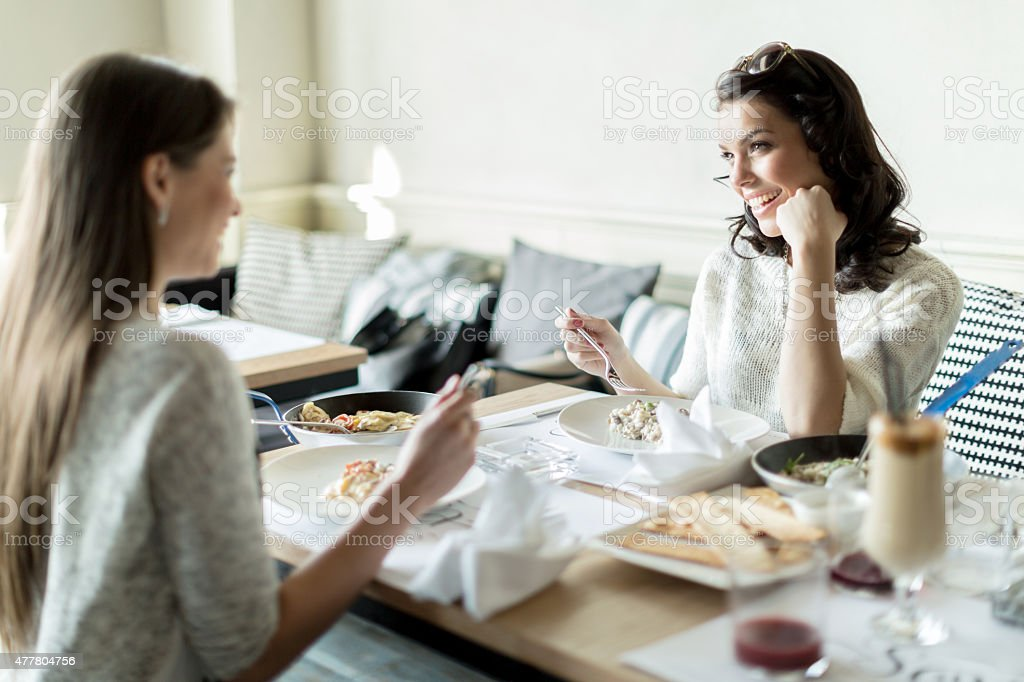 Two ladies eating in a restaurant while having a conversation stock photo