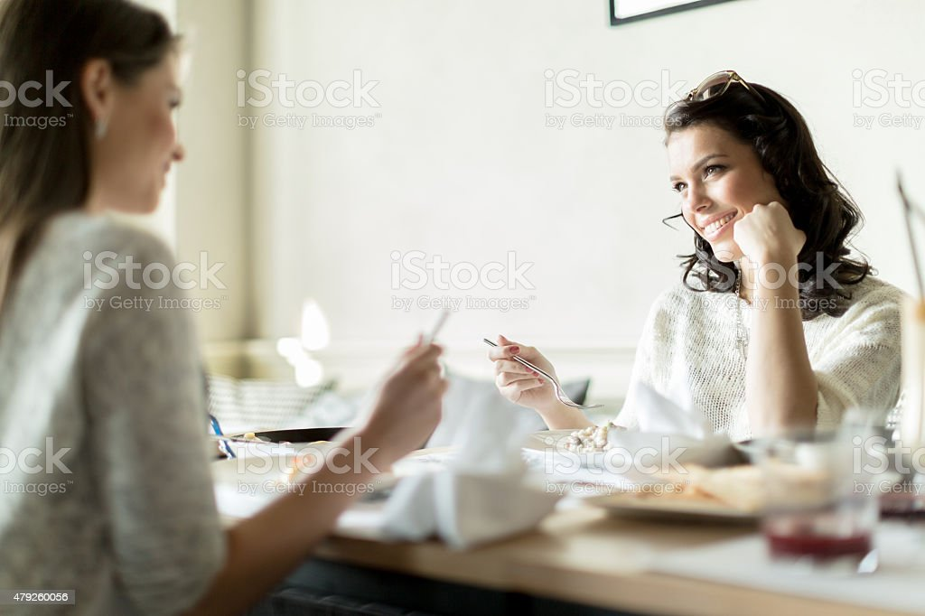 Two ladies eating in a restaurant while having a conveversation stock photo