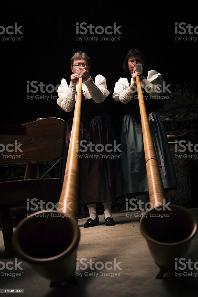 two ladies playing the alpenhorn royalty-free stock photo
