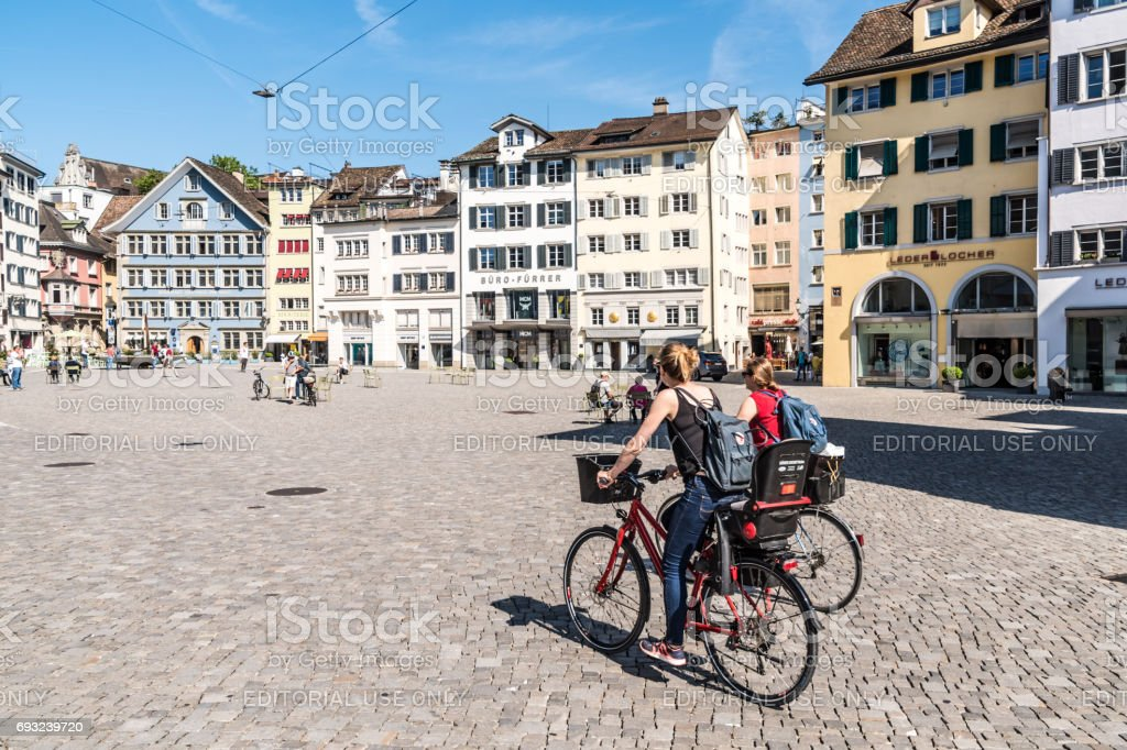 Two ladies ride bikes in town square in Zurich stock photo