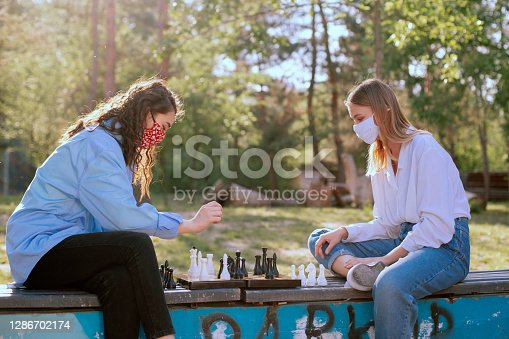 Two lady playing chess and having a chat.