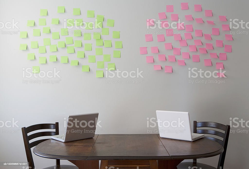 Two laptops on table, adhesive notes on wall foto de stock royalty-free