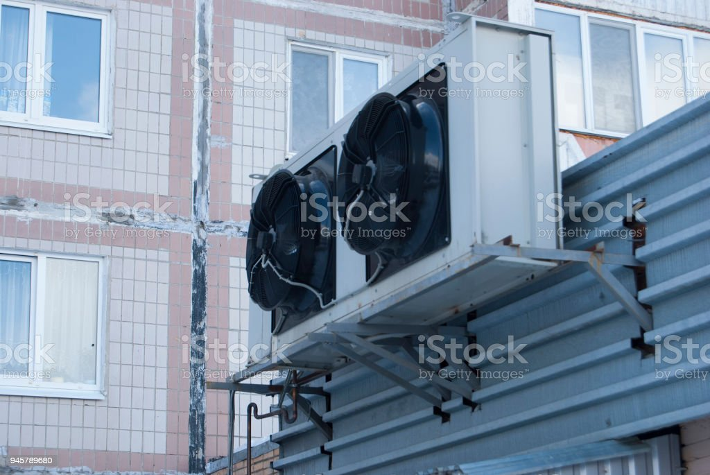 Two large black industrial fans from the air conditioner on the wall...