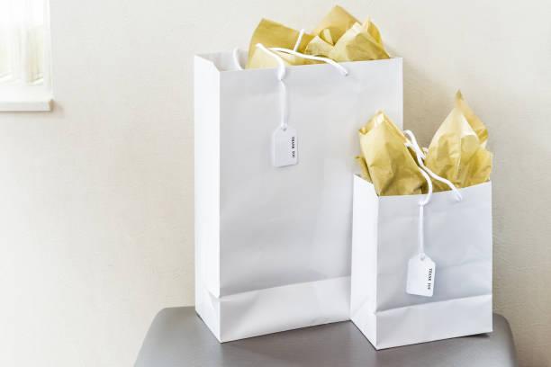zwei große geschenktüten mit dankeschön beachten sie textmarkierungen auf stuhl tisch im zimmer isoliert, goldgelb geschenkpapier von fenster wand closeup - partylabels stock-fotos und bilder