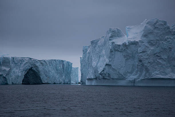 Two large icebergs with small cave stock photo
