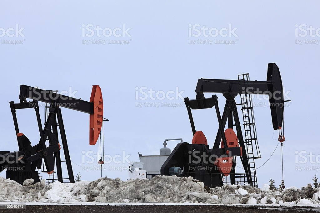 Two Large Oil Pump Jacks Drilling In The Winter royalty-free stock photo