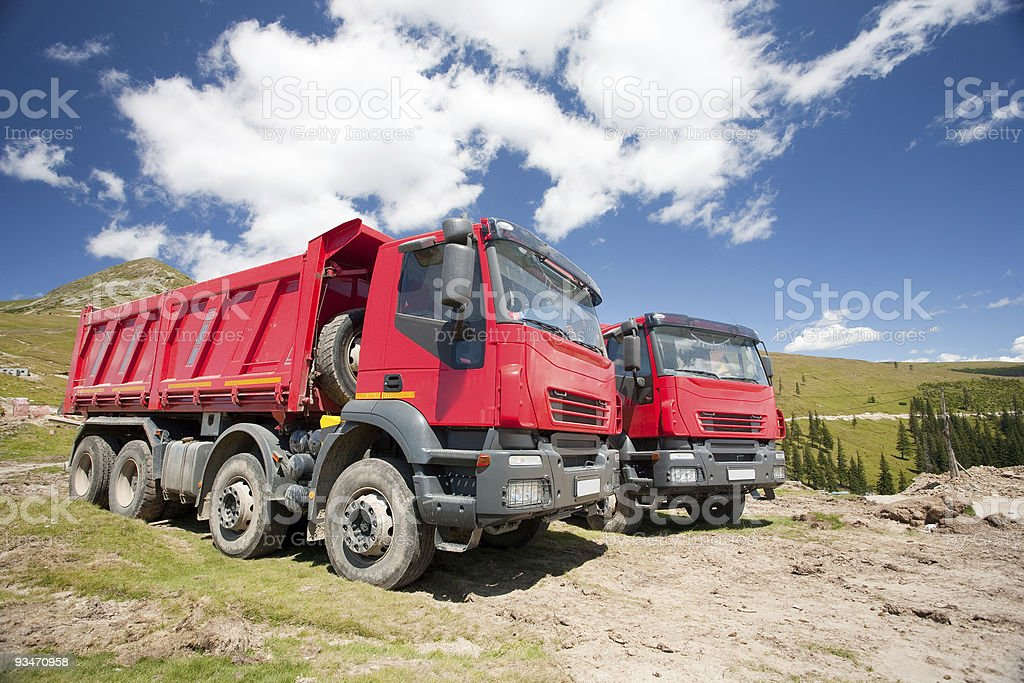 Two large red dump trucks royalty-free stock photo