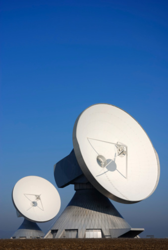 Two Large Satellite Dishes Against Clear Blue Sky Stock Photo - Download Image Now
