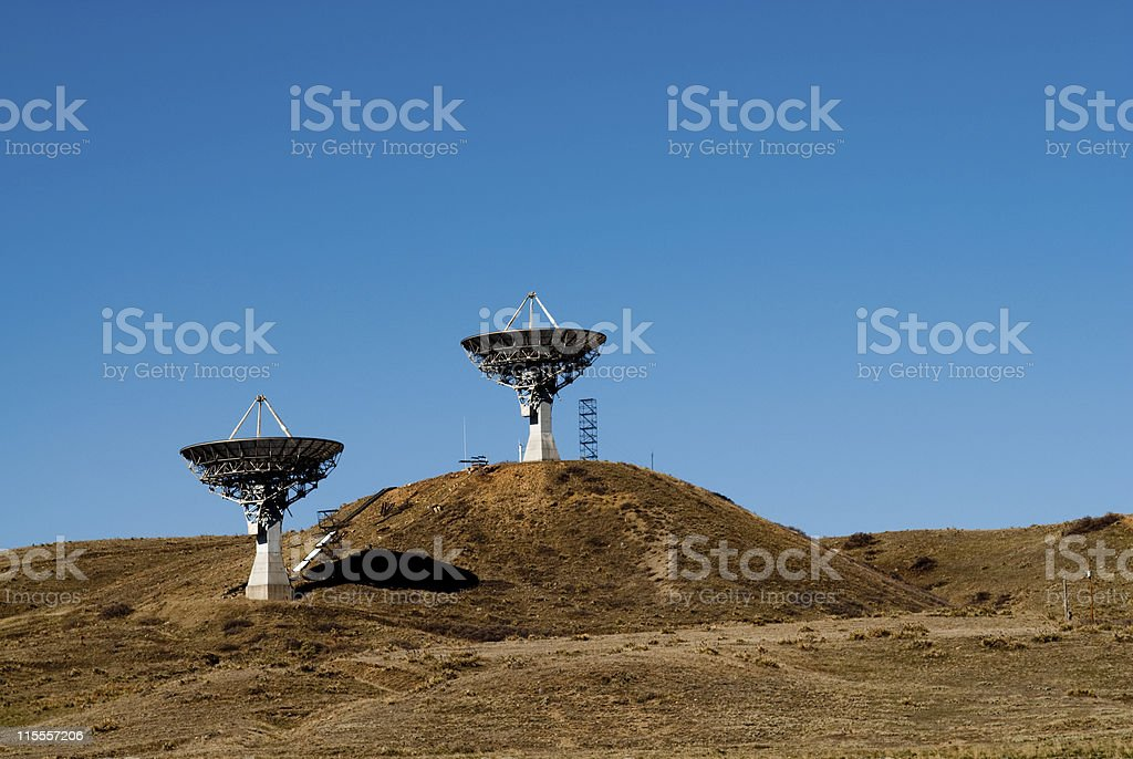 Two Large Satellite Dishes Pointing Skyward stock photo