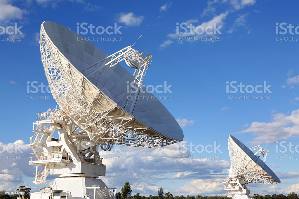 Two large satellites against a blue sky stock photo
