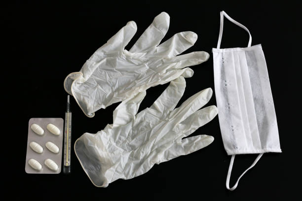 Two latex gloves, thermometer, tablets and medical mask stock photo