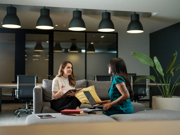 Two latin businesswomen sitting and discussing at work stock photo