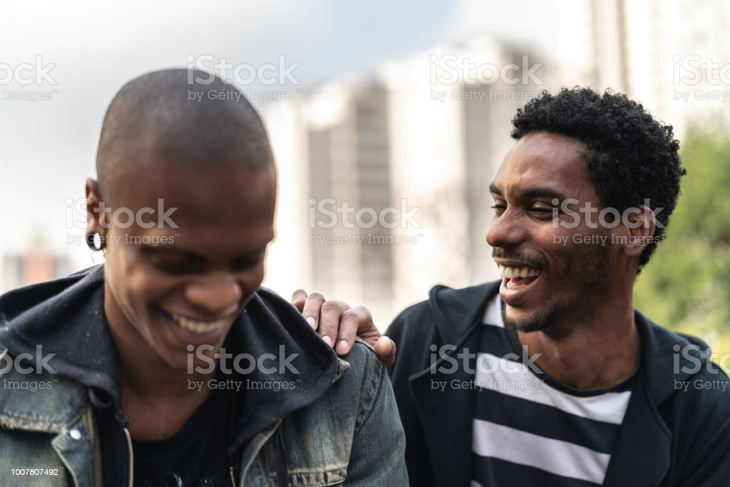 Two latino african male friends laughing stock photo