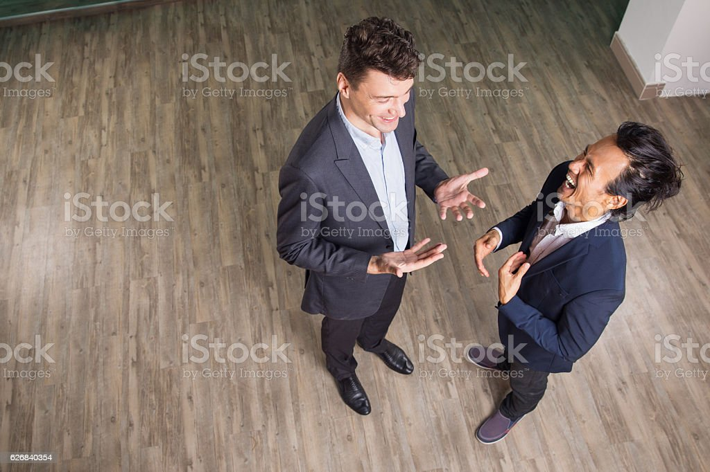 Two joyful middle-aged business men chatting, laughing, gesturing,...