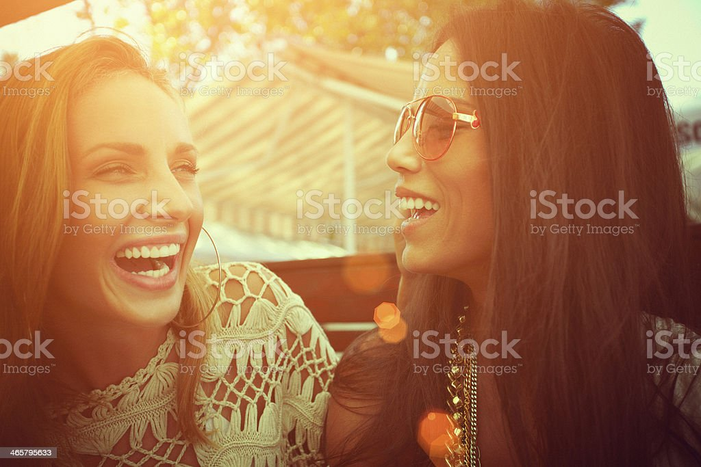Two laughing friends with sunlight shining behind royalty-free stock photo