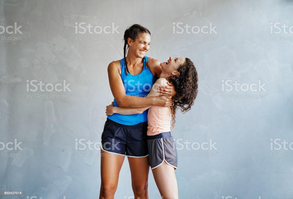 Två skrattande flickvänner kramar varandra efter ett träningspass - Royaltyfri Aktiv livsstil Bildbanksbilder