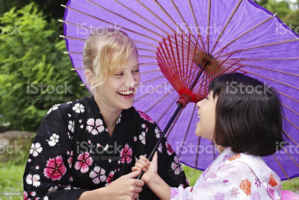 Two laughing girls wearing japanese kimono royalty-free stock photo
