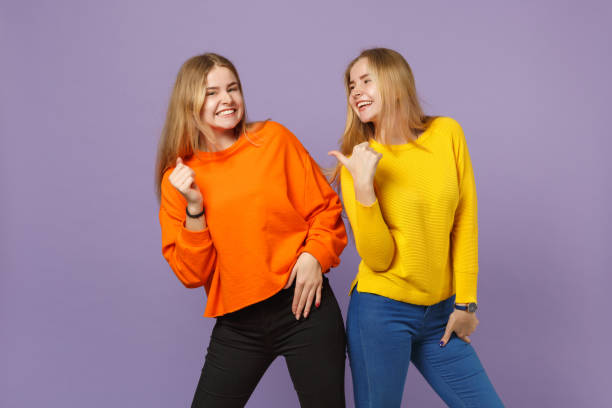 Two laughing joyful young blonde twins sisters girls in vivid co stock photo