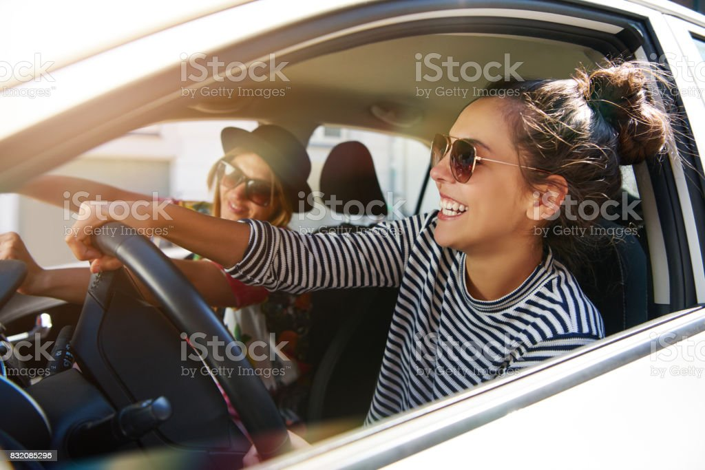 Two laughing young girlfriends driving together in a car Two attractive young girlfriends wearing sunglasses talking and laughing together while driving in a car through the city on a sunny day Adult Stock Photo