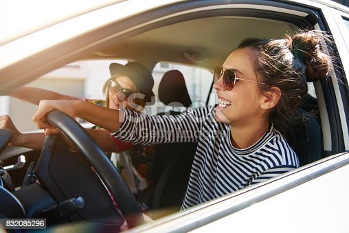 832085296 istock photo Two laughing young girlfriends driving together in a car 832085296