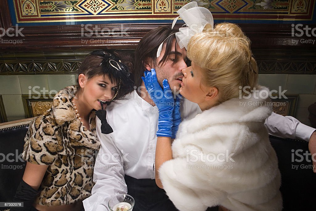 Two lavishly dressed women flirting with a man royalty-free stock photo
