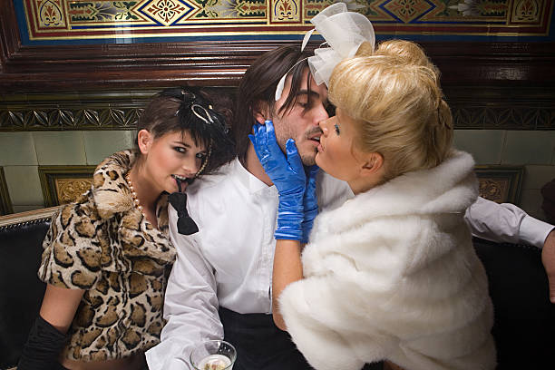 two lavishly dressed women flirting with a man - man dominating woman stock photos and pictures