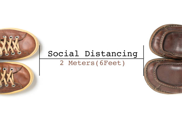 Two leather shoes keep spaced between each other for social distancing. stock photo