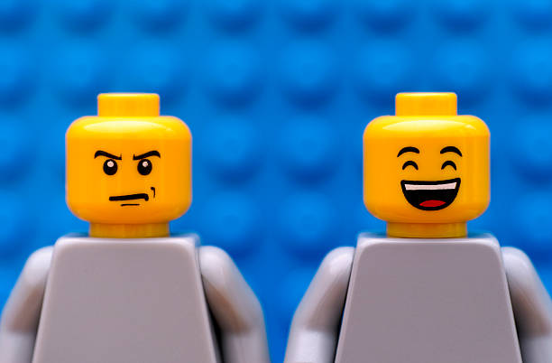two lego minifigures - strict and happy - frowning stock photos and pictures
