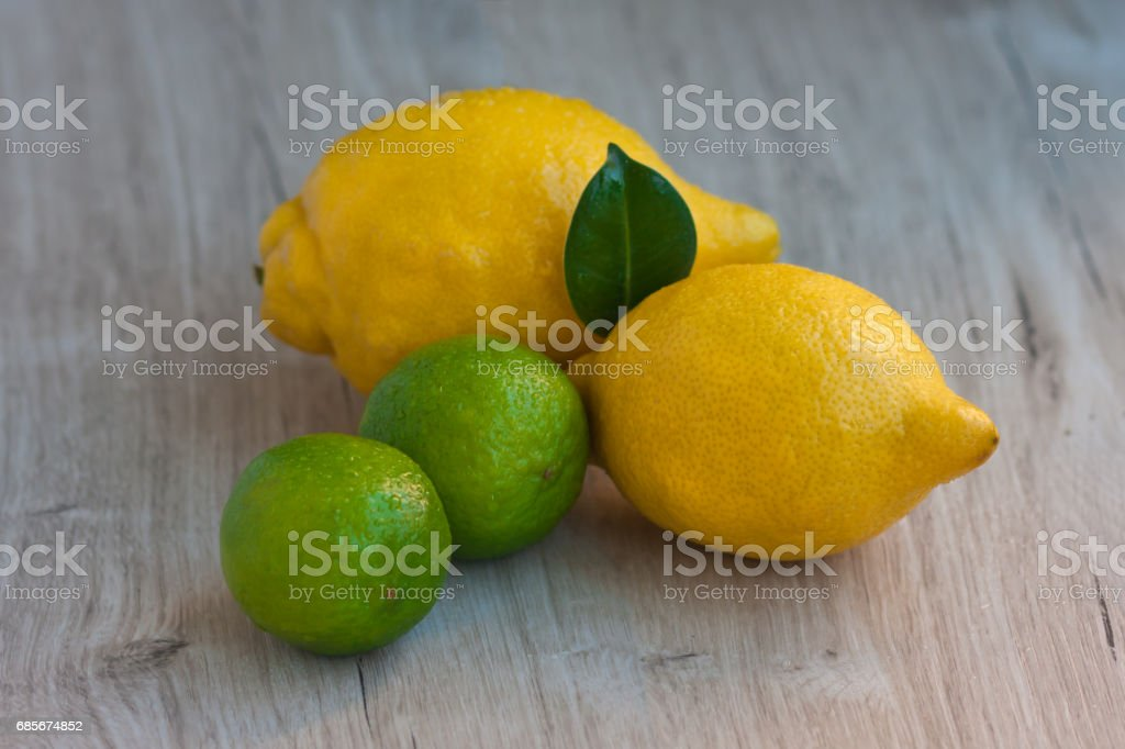 Two lemons and two limes on a rustic table foto de stock royalty-free
