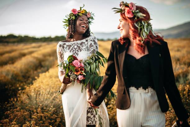 Two lesbian brides walking in the flower field stock photo