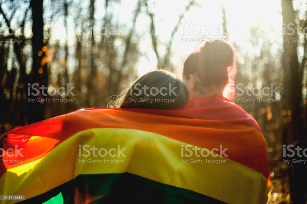 Two lesbians are embracing the gay flag royalty-free stock photo
