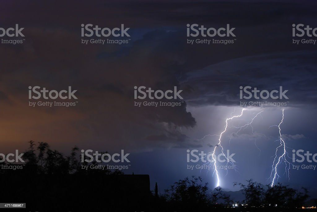 Two lightning bolts illuminating a cloudy sky at sunset stock photo