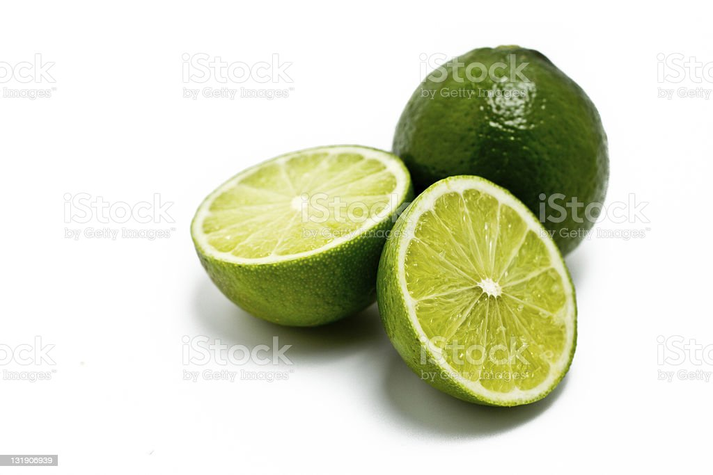 Two limes and one is sliced in half stock photo