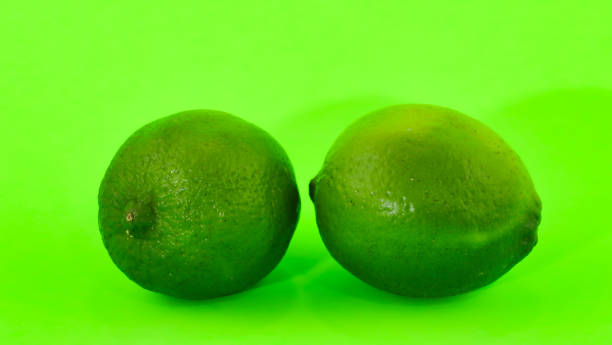 Two limes in close-up on a fluorescent green background stock photo