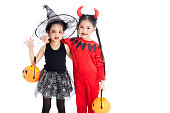 istock Two Little asian girl with face-paint in devil halloween and witch dress costume white background 1167791416