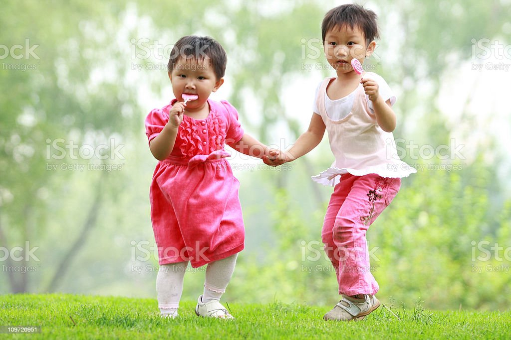Two Little Asian Girls Holding Hands and Eating Candy Outside - Stock image  .