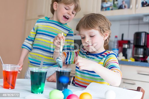 505657693 istock photo Two little blond kid boys coloring eggs for Easter holiday 497829772