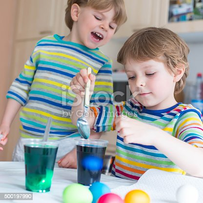 505657693 istock photo Two little blond kid boys coloring eggs for Easter holiday 500197990