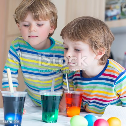 505657693 istock photo Two little blond kid boys coloring eggs for Easter holiday 513761294