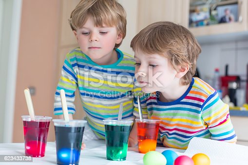 505657693 istock photo Two little blond kid boys coloring eggs for Easter holiday 623433738