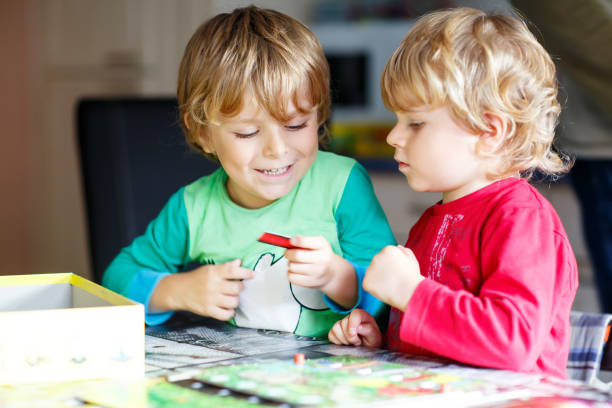 Two little blond kid boys playing together board game at home. Funny siblings having fun. stock photo