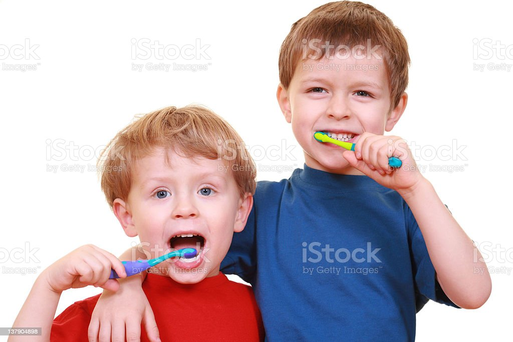 Two little boys brushing teeth with a smile in their face royalty-free stock photo