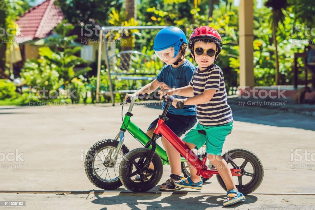 Two little boys children having fun on Balance Bike on a country tropical road stock photo